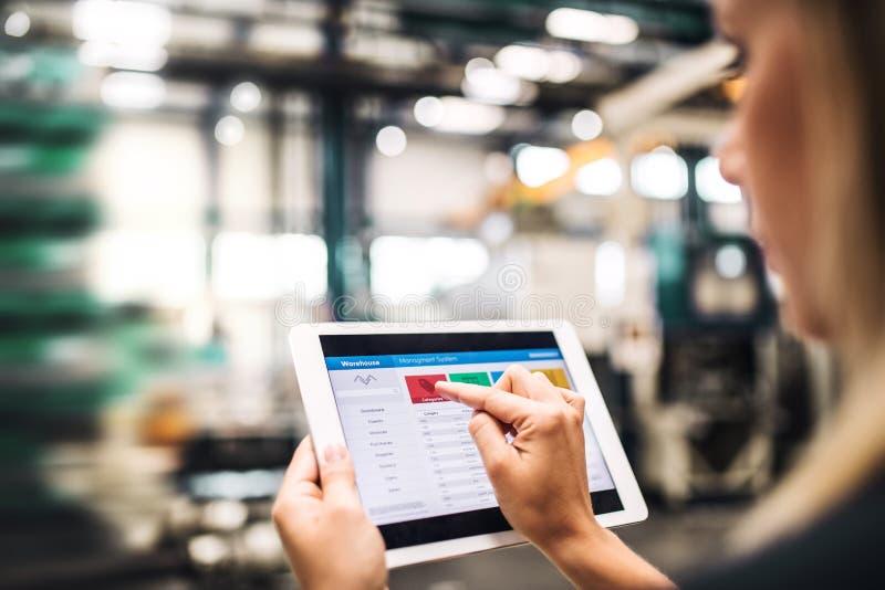 Промышленный инженер женщины в фабрике используя планшет стоковое фото rf