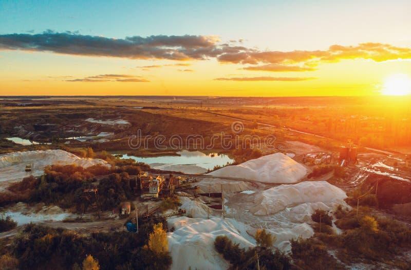 Промышленный карьер, холмы белого мела и промышленное выкапывая машинное оборудование на заходе солнца, виде с воздуха с космосом стоковые изображения