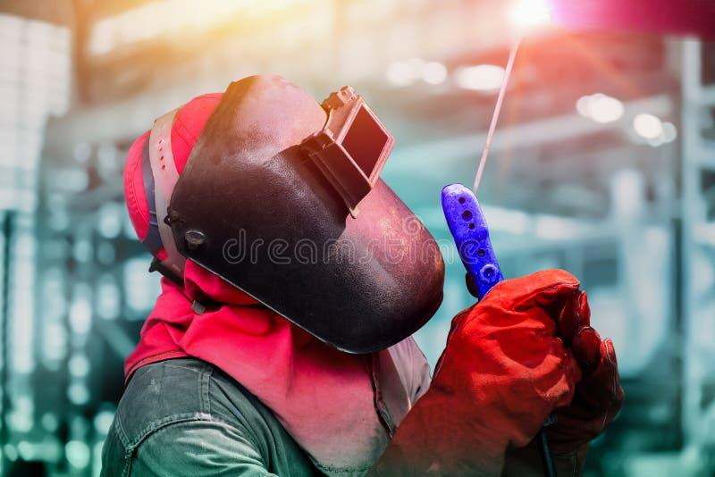 Промышленный работник на фабрике сваривая отростчатый конец вверх с защитным оборудованием стоковые фотографии rf