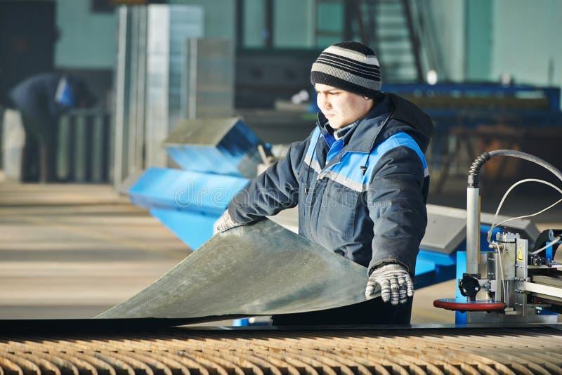 Промышленный работник подготавливая металлический лист для вырезывания плазмы на мастерской стоковые изображения rf