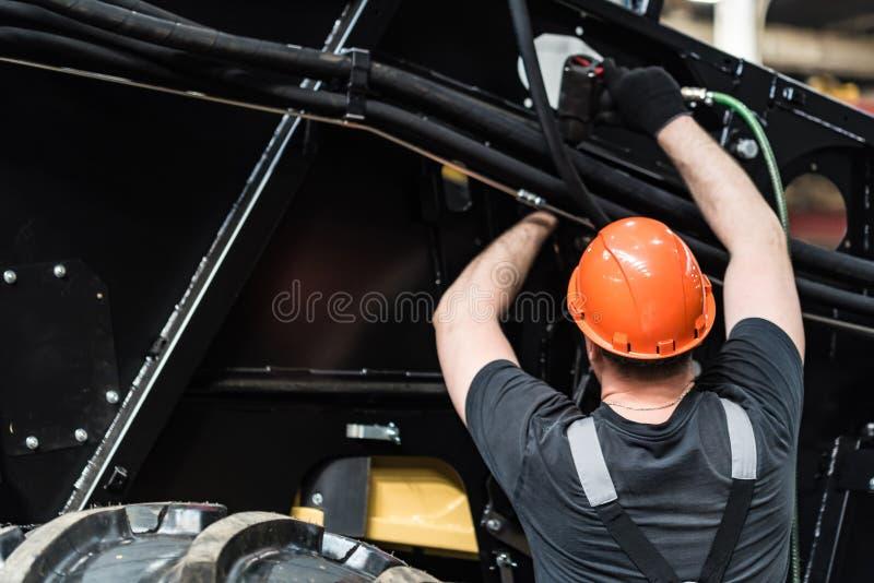 Промышленный работник собирает аграрное оборудование стоковое изображение