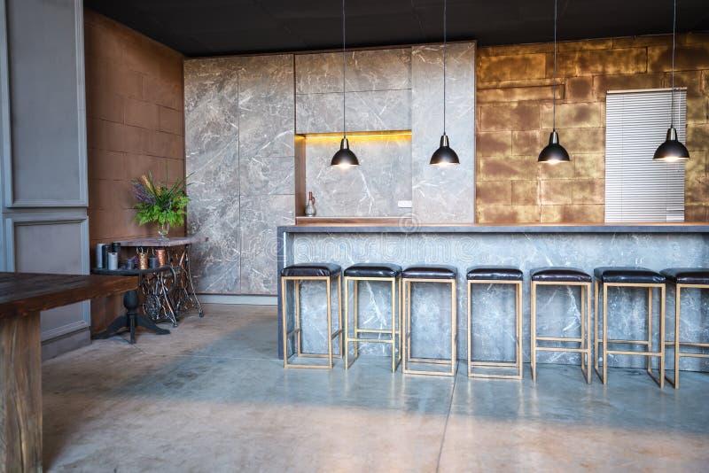 Промышленный стиль бара просторной квартиры Комната имеет много стулья на баре, 4 свисая лампы стоковое фото rf