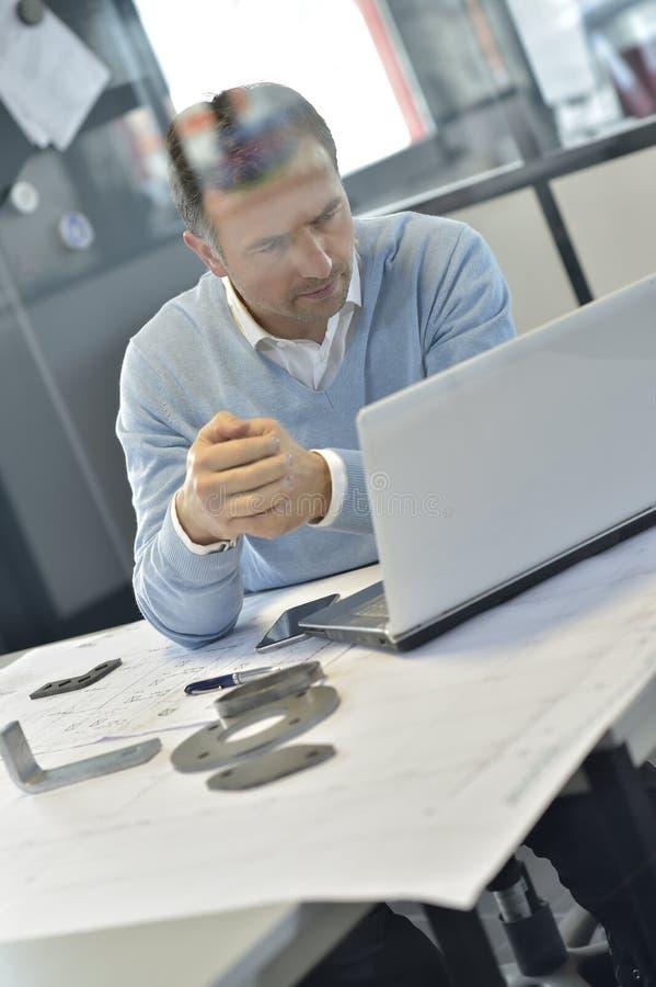 Промышленный менеджер работая на компьтер-книжке стоковое фото