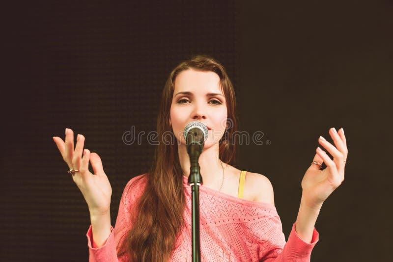 Проповедник детенышей довольно женский говоря в mic стоковое фото