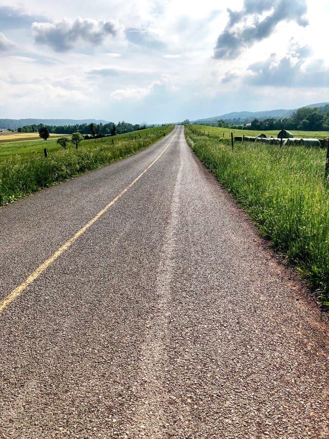 Проселочная дорога летом водя вас вверх в яркое голубое небо стоковые изображения rf