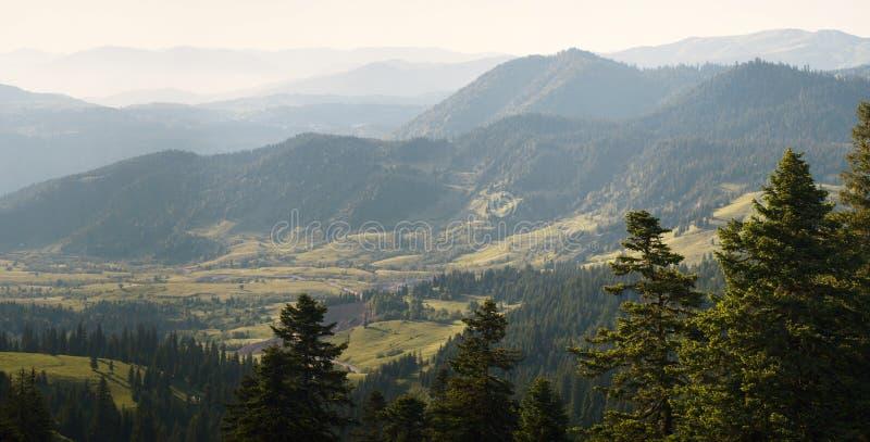 Проселочная дорога протягивая к горизонту между горными цепями Панорама ландшафта гор стоковые фото