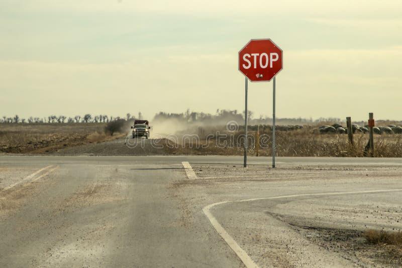 Проселочные дороги - остановите знак с большим пулевым отверстием готовит перекрестки с грузовым пикапом с трейлером управляя к н стоковое изображение