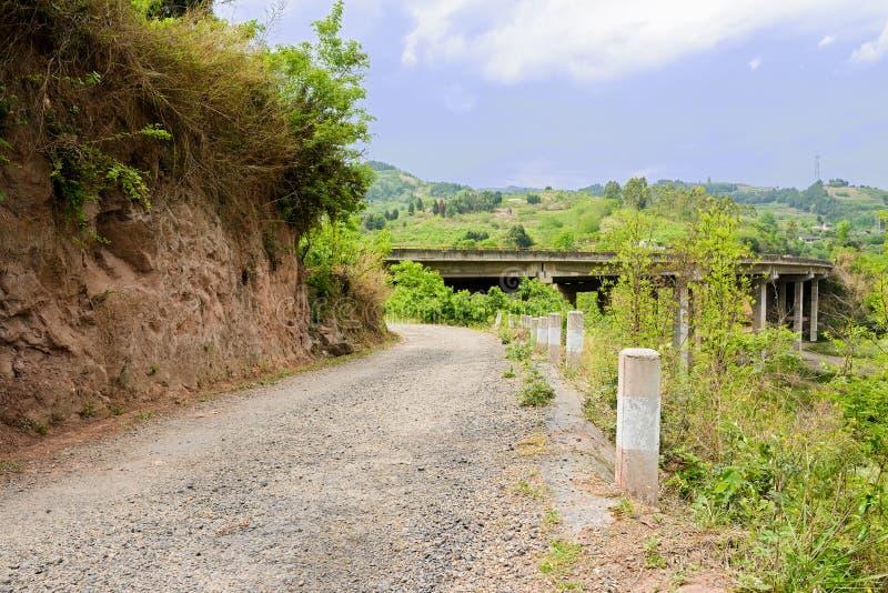 Проселочная дорога горных склонов перед автодорожным мостом в солнечной весне стоковая фотография rf