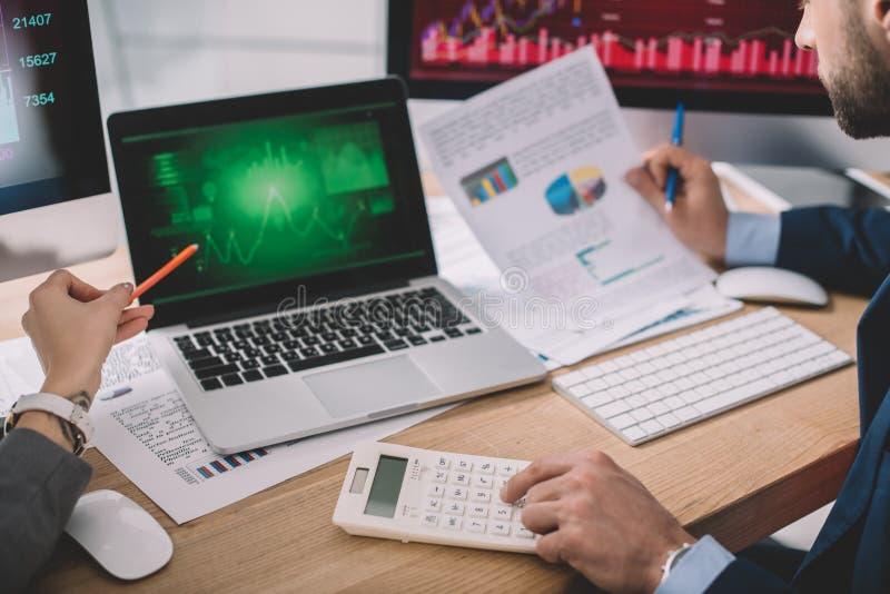 Просмотр аналитиков информационной безопасности с помощью калькулятора и графиков на мониторах компьютеров во время работы в офис стоковая фотография