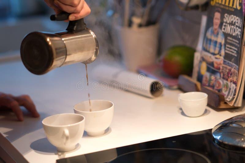 Проспите вверх, льющ кофе от бака moka стоковая фотография