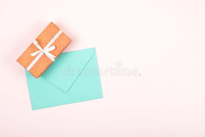 Простая подарочная коробка украшенная с белыми лентой смычка и конвертом бирюзы на пастельной розовой предпосылке r стоковые изображения rf