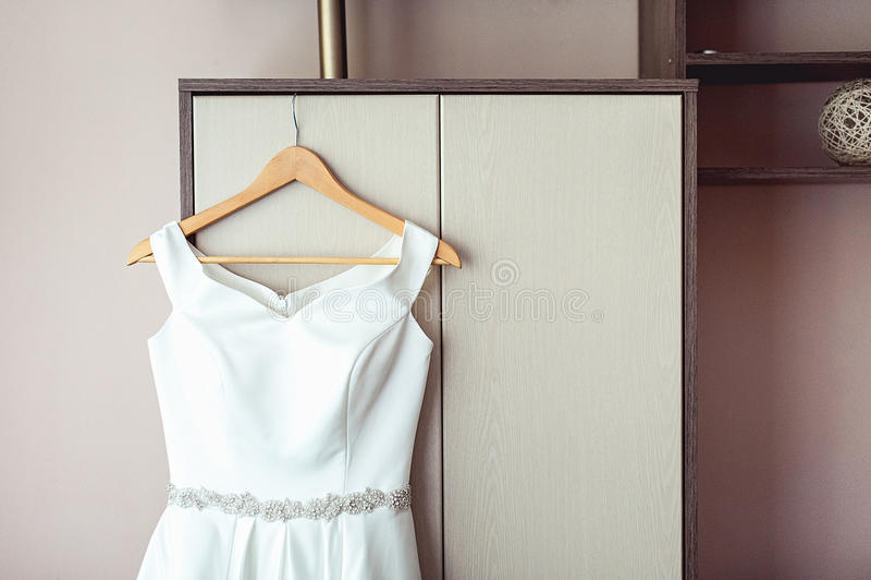 Простое белое платье свадьбы на шкафе на шкафе стоковое изображение rf