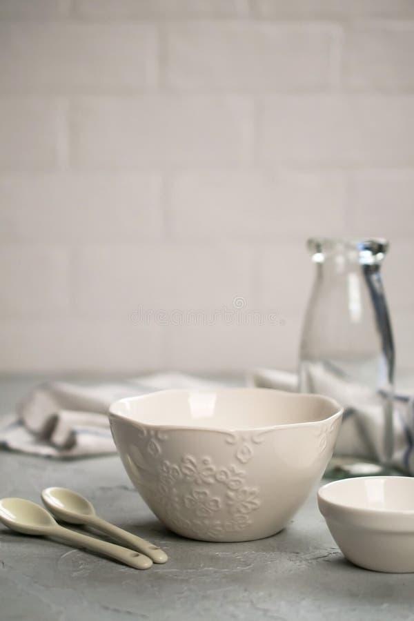 Простой домашний натюрморт кухни на предпосылке светлых стен на серой конкретной таблице Комплект блюд фарфора и стеклянной бутыл стоковые фотографии rf