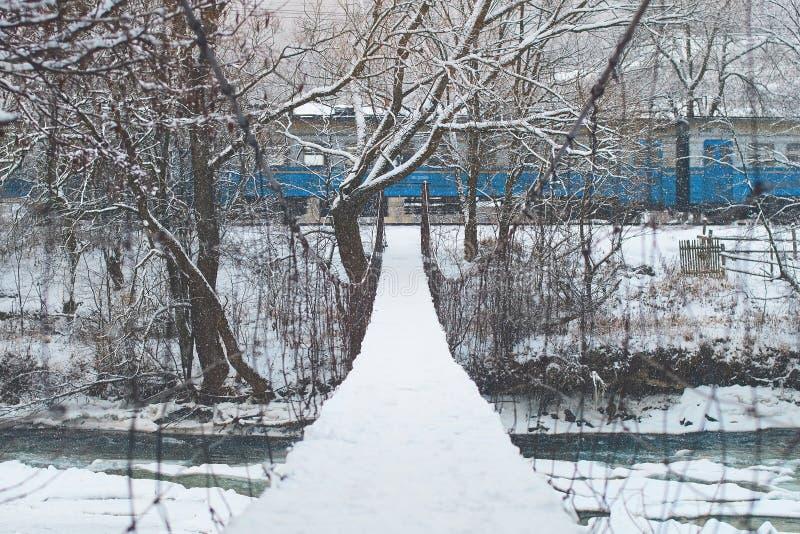 Простой мост веревочки подвеса вися над рекой горы покрытым с снегом при поезд проходя на предпосылку зимы стоковые изображения rf