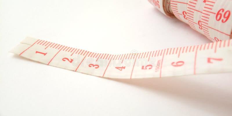Простой схематический макрос, иллюстрация для контролировать что-то, розовый пластиковый метр портноя на белой предпосылке стоковая фотография rf