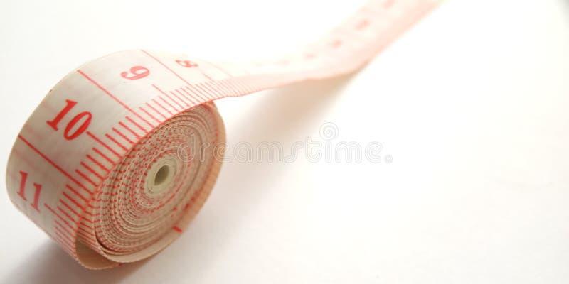 Простой схематический макрос, иллюстрация для контролировать что-то, розовый пластиковый метр портноя на белой предпосылке стоковые фото