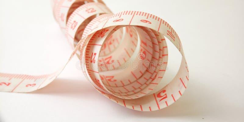 Простой схематический макрос, иллюстрация для контролировать что-то, розовый пластиковый метр портноя на белой предпосылке стоковое фото rf