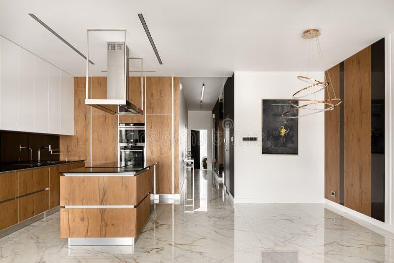 Просторная кухня с островными и деревянными элементами стоковые фото