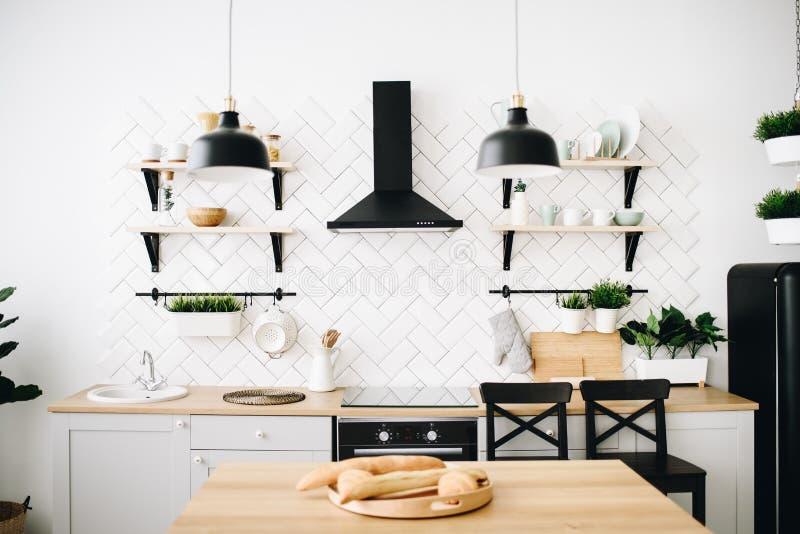 Просторная современная скандинавская кухня просторной квартиры с белыми плитками и черными приборами E Багеты на заводе во фронте стоковое фото rf