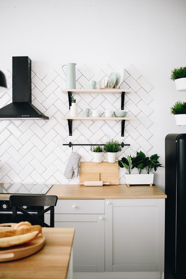 Просторная современная скандинавская кухня просторной квартиры с белыми плитками и черными приборами Светлая комната E r стоковая фотография rf