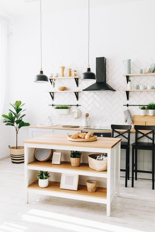 Просторная современная скандинавская кухня просторной квартиры с белыми плитками и черными приборами Светлая комната E стоковые фотографии rf