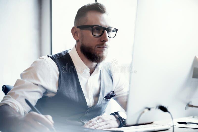 Просторной квартиры работы жилета рубашки стекел молодого человека портрета бородатый стильный нося проект белой современной онла стоковое фото rf