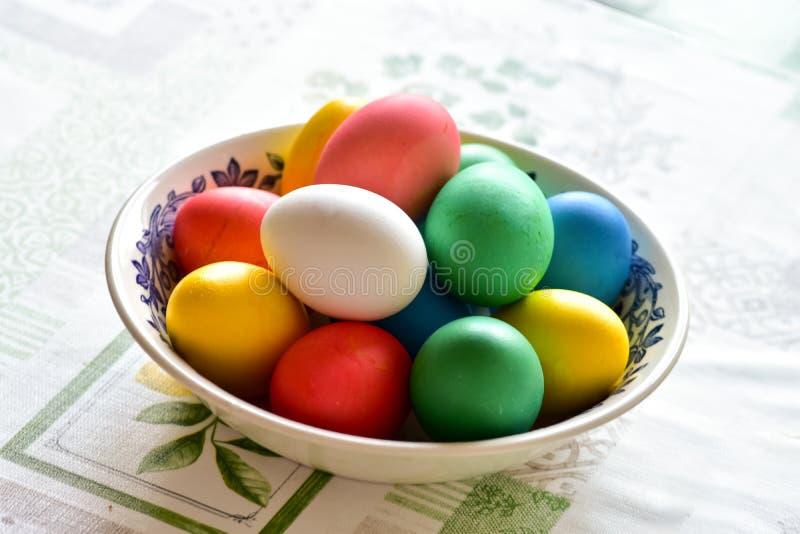 Простые моменты действительности - чашка с покрашенными пасхальными яйцами на таблице стоковые фотографии rf