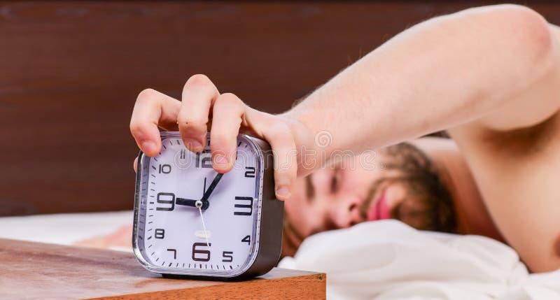 Просыпать ленивого человека счастливый вверх в руках кровати поднимая в утре со свежим чувством расслабленным Красивый человек зе стоковое изображение rf