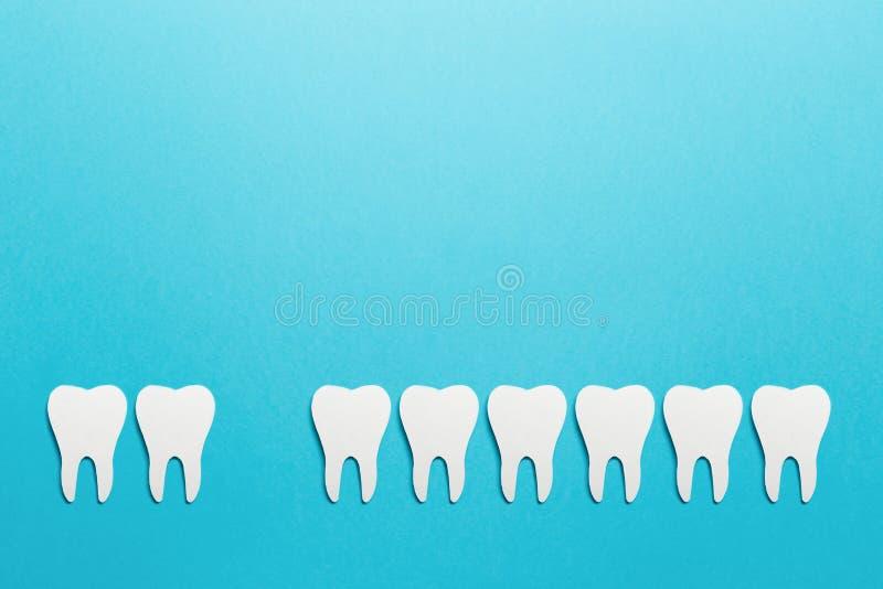 Протезно-зубоврачебная стоматология Белые зубки на синем фоне Устная гигиена зубов Концепция психического здоровья Ремонт зубов стоковое фото