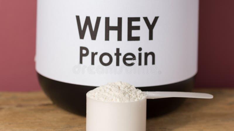 Протеин Whey Закройте вверх ветроуловителя с ванильным порошком и черным ja стоковое изображение rf