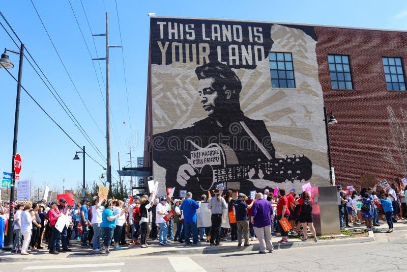 Протестующие маршируют настенной росписью Woody Guthrie которая говорит фашистам убийств этой машины на протесте в марте на всю ж стоковая фотография
