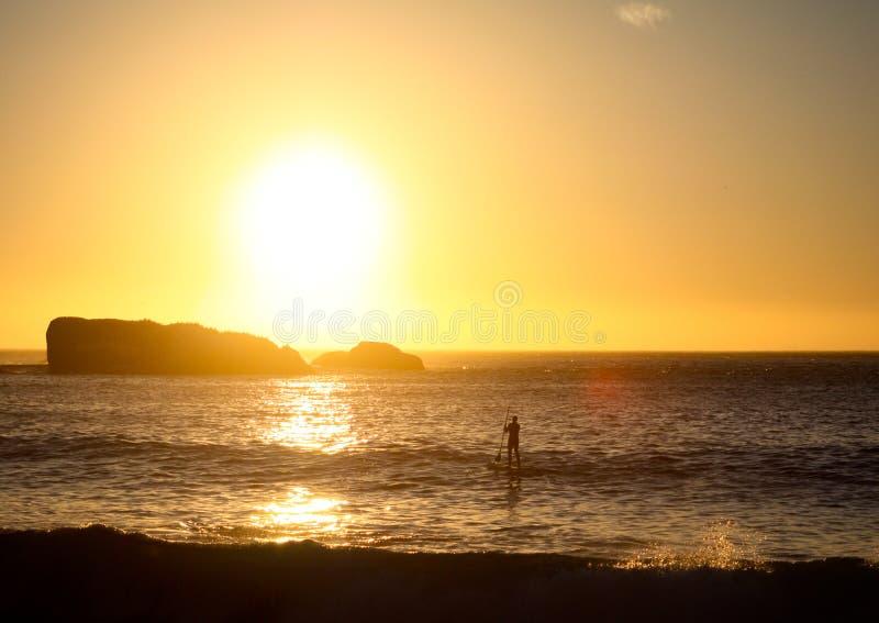противостоьте заход солнца sufer стойки затвора вверх стоковые фото