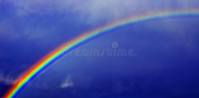 против голубого неба радуги стоковые изображения rf