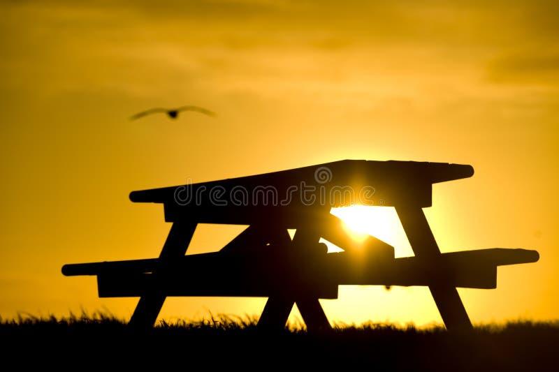 против пикника стенда silhouetted заход солнца стоковое изображение