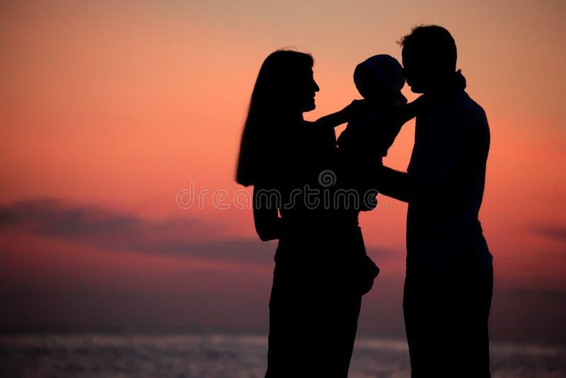 против склонения семья вручает силуэты моря стоковые фото