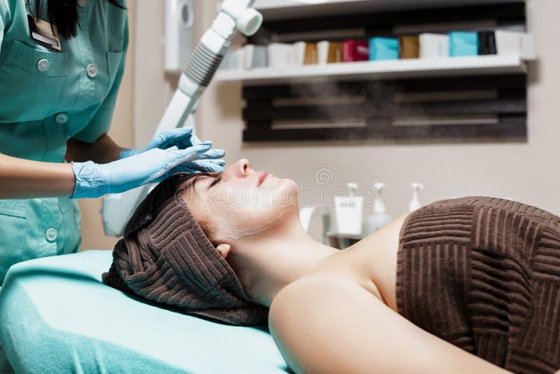 Против старения лицевой массаж cosmetologist делая массаж для молодой женщины на салоне курорта стоковая фотография rf