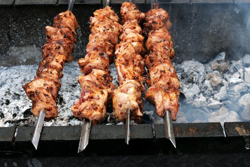 Протыкальники мяса свинины или говядины зажарены на горячих углях в барбекю или гриле, жарком на протыкальниках металла Показывае стоковая фотография