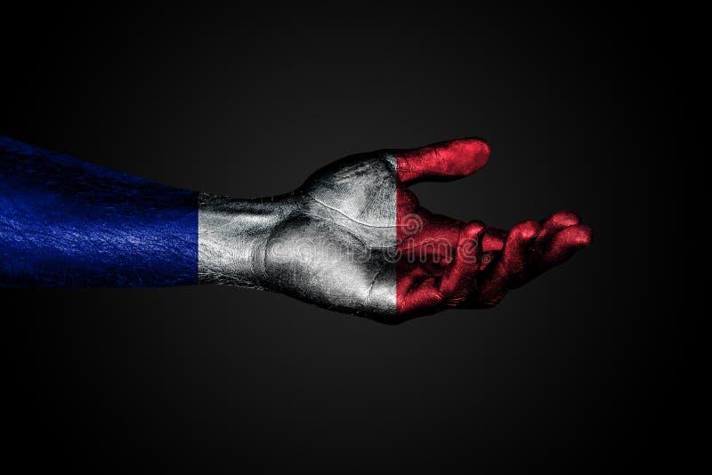 Протягиванная рука с вычерченным флагом Франции, знак помощи или запрос, на темной предпосылке стоковое фото