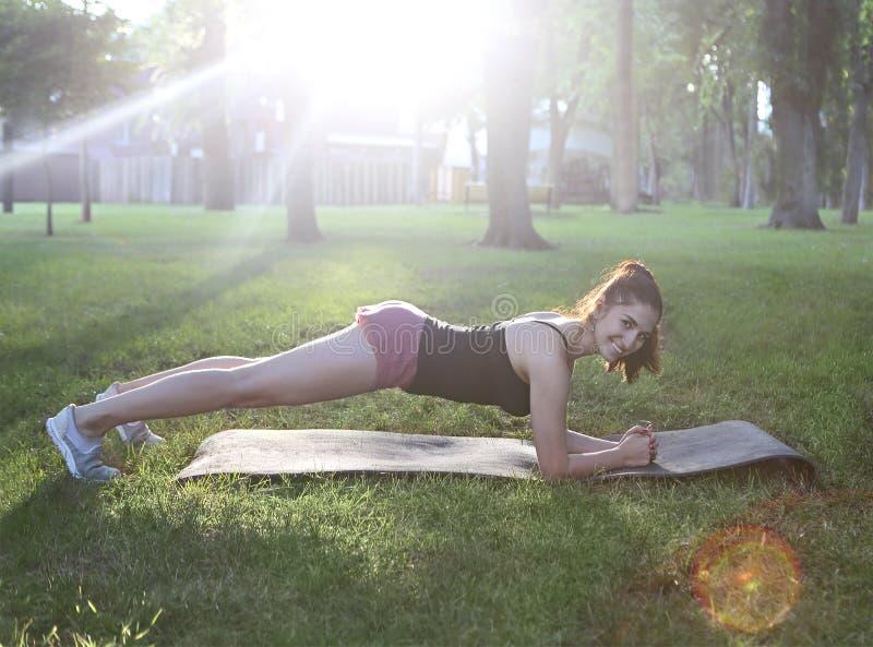 Протягивать женщину в простирании внешней тренировки усмехаясь счастливом делая стоковая фотография