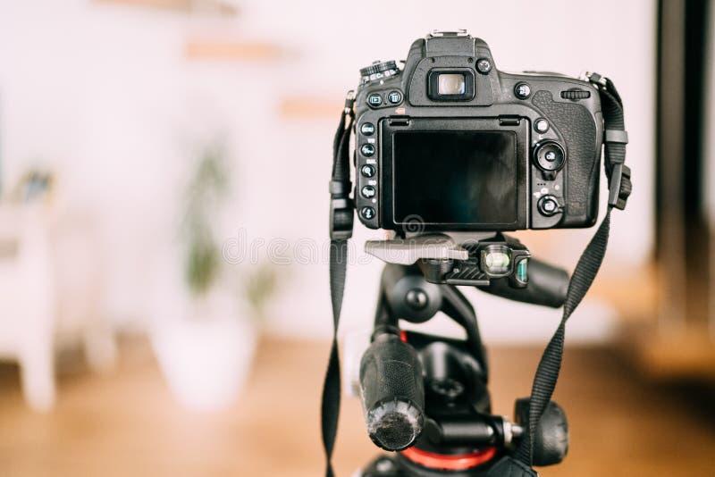 профессиональная камера сидя на треноге и принимая фотоснимки Шестерня фотографии дизайна интерьера стоковые фото