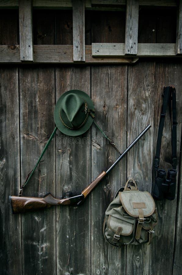 Профессиональное оборудование охотников для охотиться Винтовка, шляпа, сумка и другие на деревянной черной предпосылке стоковая фотография rf