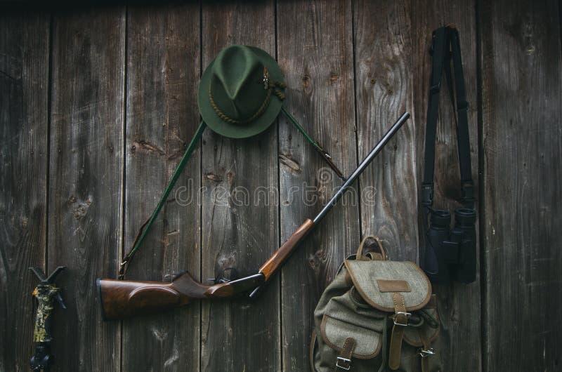 Профессиональное оборудование охотников для охотиться Винтовка, шляпа, сумка и другие на деревянной черной предпосылке стоковое фото