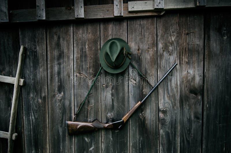 Профессиональное оборудование охотников для охотиться Винтовка, шляпа, сумка и другие на деревянной черной предпосылке стоковые фотографии rf