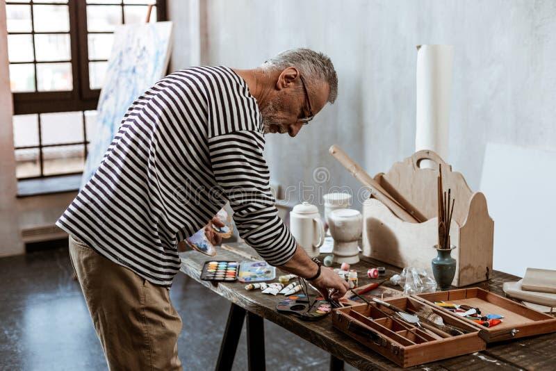 Профессиональное опытное положение художника около таблицы с краскам стоковое фото rf