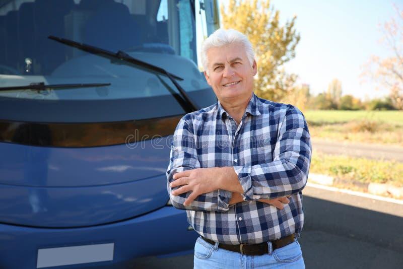 Профессиональное положение водителя около автобуса стоковая фотография rf