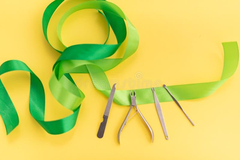 Профессиональные инструменты набора маникюра для заботы ногтя на желтой предпосылке с зеленым смычком r r стоковые фото