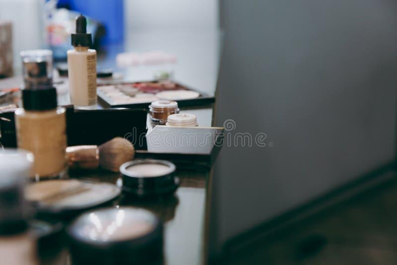 Профессиональные косметики лежат на таблице в салоне красоты стоковые фото