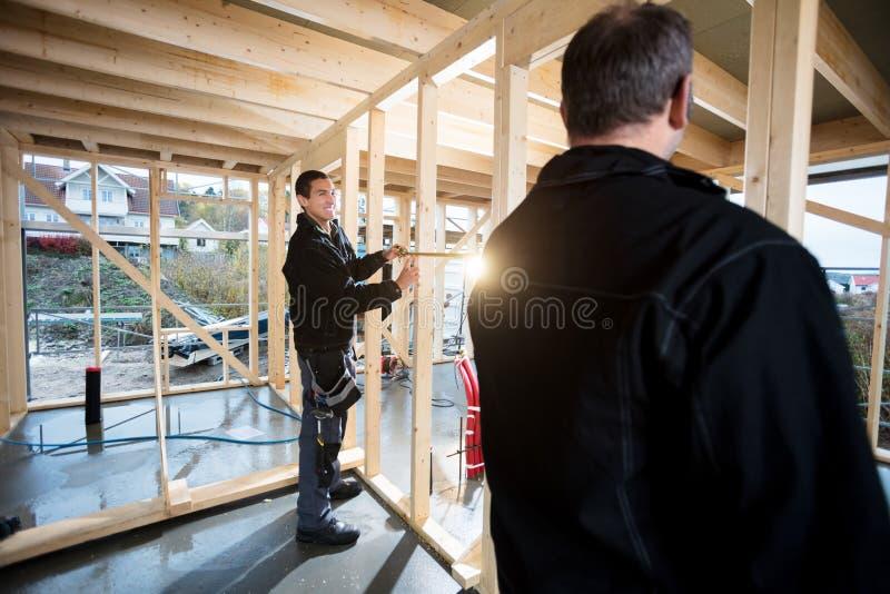 Профессиональные плотники измеряя деревянные штендеры на месте стоковые изображения rf