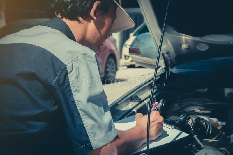 Профессиональные техники ремонта автомобиля проверяют двигатель согласно документам контрольного списока для обеспечения что они  стоковые изображения rf