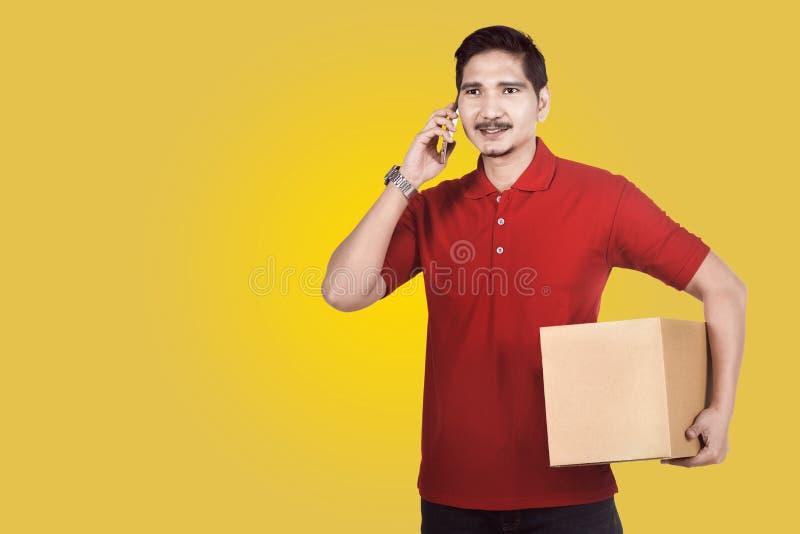 Профессиональный азиатский работник доставляющий покупки на дом используя телефон пока носящ parce стоковая фотография
